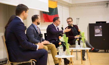 Nuotraukoje visi 4 dalyviai diskutuoja. Šalia matosi moderatorius.